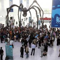 Photo - Local and international activists march inside a conference center under a giant statue of a spider to demand urgent action to address climate change at the U.N. climate talks in Doha, Qatar, Friday, Dec. 7, 2012. A dispute over money clouded U.N. climate talks Friday, as rich and poor countries sparred over funds meant to help the developing world cover the rising costs of mitigating global warming and adapting to it. (AP Photo/Osama Faisal)