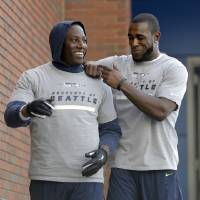 Photo - Seattle Seahawks defensive end Chris Clemons, left, and safety Kam Chancellor joke as they head to the New York Giants' NFL practice facility for a final walkthrough Saturday, Feb. 1, 2014, in East Rutherford, N.J. The Seahawks and the Denver Broncos are scheduled to play in the Super Bowl XLVIII football game Sunday, Feb. 2, 2014. (AP Photo/Jeff Roberson)
