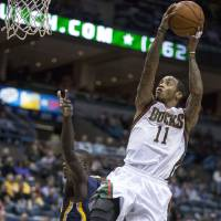 Photo -   Milwaukee Bucks' Monta Ellis, right, leaps through the lane for a layup against the Indiana Pacers defense during the first half of an NBA basketball game on Wednesday, Nov. 14, 2012, in Milwaukee. (AP Photo/Tom Lynn)