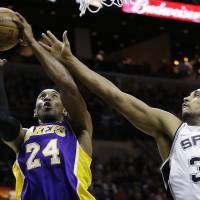 Photo - Los Angeles Lakers' Kobe Bryant (24) pulls down a rebound in front of San Antonio Spurs' Boris Diaw (33), of France, during the first quarter of an NBA basketball game on Wednesday, Jan. 9, 2013, in San Antonio. (AP Photo/Eric Gay)