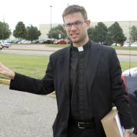 Photo - Oklahoma City clergyman Lance Schmitz holds petitions that he attempted to deliver to Hobby Lobby's corporate headquarters Thursday in Oklahoma City.   PAUL HELLSTERN - Oklahoman