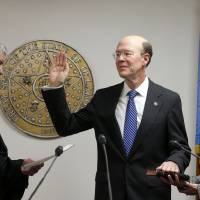 Photo - Chief Justice Steven W. Taylor swears in Bob Anthony to his fifth term on the Oklahoma Corporation Commission on Thursday. Anthony's wife, Nancy, holds the Bible.