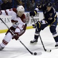 Photo - Phoenix Coyotes' Antoine Vermette, left, controls the puck as St. Louis Blues' Jay Bouwmeester defends during the first period of an NHL hockey game on Thursday, April 18, 2013, in St. Louis. (AP Photo/Jeff Roberson)