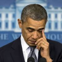 Photo - President Barack Obama wipes his eye as he talks about the Connecticut elementary school shooting, Friday, Dec. 14, 2012, in the White House briefing room in Washington. (AP Photo/Carolyn Kaster)
