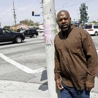 Photo -   On April 19, 2012, Henry Keith Watson poses for a portrait on the corner of Florence and Normandie in Los Angeles, where Watson and others dragged truck driver Reginald Denny from his cab and beat him severely on the first night of rioting. The acquittal of four police officers in the videotaped beating of King sparked rioting that spread across the city and into neighboring suburbs. Cars were demolished and homes and businesses were burned. Before order was restored, 55 people were dead, 2,300 injured and more than 1,500 buildings were damaged or destroyed.( (AP Photo/Matt Sayles)