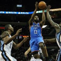 Photo - Oklahoma City Thunder guard James Harden (13) shoots under pressure by Memphis Grizzlies forward Zach Randolph (50) and forward Darrell Arthur (00) in the first half of an NBA basketball game Tuesday, Jan. 4, 2011 in Memphis, Tenn. (AP Photo/Jim Weber)