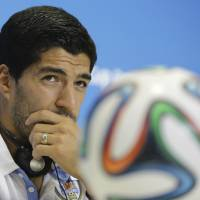 Photo - Uruguay's Luis Suarez listens to a question during a press conference, a day before his team's group D World Cup soccer match, at the Arena das Dunas in Natal, Brazil, Monday, June 23, 2014. (AP Photo/Antonio Clanni)