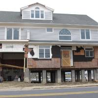 Photo - This house in Sea Bright, N.J., shown here on Jan. 15, 2013, is one of the first in the storm-devastated town to be elevated while being rebuilt. The town's entire business district was wiped out by Superstorm Sandy (four shops have since re-opened) and 75 percent of residents are still homeless. Yet Sea Bright is determined to rebuild as a debate rages on whether to restore shore communities to their pre-storm condition, or buy out properties in flood-prone areas and depopulate them. (AP Photo/Wayne Parry)