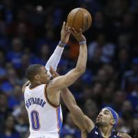 Photo - Oklahoma City Thunder guard Russell Westbrook (0) shoots over Memphis Grizzlies guard Jerryd Bayless (7) in the second quarter of an NBA basketball game in Oklahoma City, Thursday, Jan. 31, 2013. Oklahoma City won 106-89. (AP Photo/Sue Ogrocki)