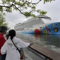 Photo - FILE - In this May 8, 2013, file photo, people pause to look at Norwegian Cruise Line's new ship, Norwegian Breakaway, on the Hudson River, in New York. A 4-year-old child died after being pulled unresponsive from a swimming pool on the Norwegian Breakaway, off the coast of North Carolina on Monday, Feb. 3, 2014, cruise line and Coast Guard officials said. Crew members were able to revive a 6-year-old boy also found in the pool. He was airlifted to a hospital, where his condition was unknown. (AP Photo/Richard Drew, File)