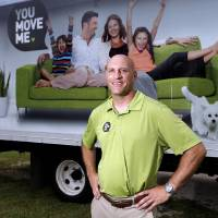 Photo - Andrew Wilson, owner  of You Move Me, poses in front of his van. Photo by Sarah Phipps, The Oklahoman  SARAH PHIPPS - SARAH PHIPPS