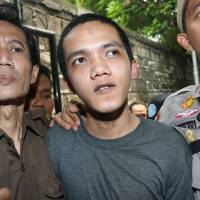 Photo - Child sexual abuse suspect Agun Iskandar, center, is escorted by security officers upon arrival for his trial at district court in Jakarta, Indonesia, Tuesday, Aug. 26, 2014. The first of five janitors accused of raping a kindergartner in a bathroom at a prestigious international school went on trial Tuesday. (AP Photo/Tatan Syuflana)