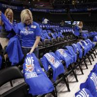 Photo - Kelly Curry (left) and Khrystian Hembree put t-shirts on chairs in preparation for the first game of the NBA basketball finals at the Chesapeake Arena on Tuesday, June 12, 2012 in Oklahoma City, Okla.  Photo by Steve Sisney, The Oklahoman