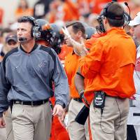 Photo - With the absence of an offensive coordinator, Oklahoma State coach Mike Gundy, left, has essentially been the leader in quarterback meetings.  Photo by Sarah Phipps, The Oklahoman