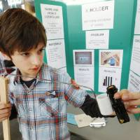 """Photo - Fourth-grader Matthew Kryvenia, 9, from Heritage Trails Elementary in Moore, shows off his flashlight holder invention, named the """"K Holder,"""" during the Oklahoma Student Inventors Exposition held at Rose State College in Midwest City. Photos by Paul B. Southerland, The Oklahoman"""