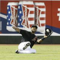 Photo - Arizona Diamondbacks' Alfredo Marte makes a sliding catch in the seventh inning to rob the Colorado Rockies' Charlie Blackmon of a hit during a baseball game, Saturday, Aug. 9, 2014, in Phoenix. (AP Photo/Darryl Webb)