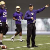 Photo - New Washington head football coach Chris Petersen, right, gives directions to his team on the first day of spring NCAA college football practice, Tuesday, March 4, 2014, in Seattle. (AP Photo/Ted S. Warren)