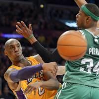Photo - Los Angeles Lakers guard Kobe Bryant, left, passes around Boston Celtics forward Paul Pierce during the first half of their NBA basketball game, Wednesday, Feb. 20, 2013, in Los Angeles. (AP Photo/Mark J. Terrill)