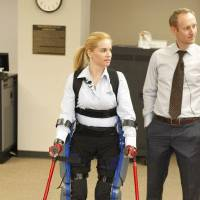Photo - Patient Agnes Fejerdy and physical therapist Phil Astrachan demonstrate  a device that helps patients walk after injuries have put them in a wheelchair.    PAUL HELLSTERN