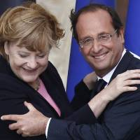 Photo -   FILE - In this July 8, 2012 file photo German Chancellor Angela Merkel, left, and French President Francois Hollande react after a speech in front of Reims cathedral, in Reims, eastern France. Merkel and Hollande said in a joint statement issued by the German government Friday, July 27, 2012 that their countries are