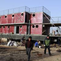 Photo - In this photo taken Nov. 24, 2012, Lu Zhenghai, right, walks near his ark-like vessel in China's northwest Xinjiang Uyghur Autonomous Region.  Lu Zhenghai is one of at least two men in China predicting a world-ending flood, come Dec. 21, the fateful day many believe the Maya set as the conclusion of their 5,125-year long-count calendar. Zhenghai has spent his life savings building the 70-foot-by-50-foot vessel powered by three diesel engines, according to state media. In Mexico's Mayan heartland, nobody is preparing for the end of the world; instead, they're bracing for a tsunami of spiritual visitors. (AP Photo/ANPF-Chen Jiansheng)
