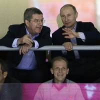 Photo - Russian President Vladimir Putin watches the USA Russia men's hockey game from a box at the 2014 Winter Olympics, Saturday, Feb. 15, 2014, in Sochi, Russia. (AP Photo/David J. Phillip )