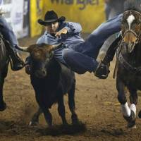 Photo - Kamry Dymmek of Kissimmee, Fla., competes in steer wrestling during the National Circuit Finals Rodeo at the State Fair Arena in Oklahoma City, Thursday, April 4, 2013. Photo by Bryan Terry, The Oklahoman