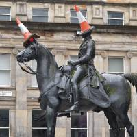 Photo - This undated photo shows a statue of the Duke of Wellington in Glasgow, Scotland. The statue is rarely seen without a traffic cone on its head. It started as a joke by students decades ago but is now an almost permanent symbol of local humor. Visiting the famous monument with its cones is one of a number of free things to see and do in Glasgow. (AP Photo/ Stewart Cunningham)