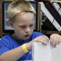 Photo - Max Emig, 8, tapes two pieces of paper together as children color and construct peace lanterns at the Edmond YMCA in Edmond, OK, Monday, July 16, 2012. The students are creating these for counterparts in Japan to coincide with anniversary of Hiroshima bombing.  By Paul Hellstern, The Oklahoman