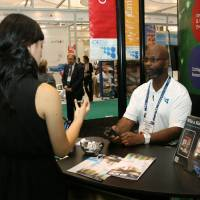 Photo - James Johnson, with the Oklahoma  Department of Commerce, chats with visitor Wednesday at the BIO International convention. PHOTO BY JIM STAFFORD  unknown