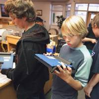 Photo - From left, eighth-graders Kyle Story, Kyle McDaniel and Dylan Ramsey line up Thursday at the Longfellow Middle School library, where students picked up their netbook computers. PHOTO BY STEVE SISNEY, THE OKLAHOMAN  STEVE SISNEY - STEVE SISNEY