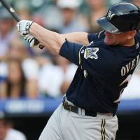 Photo - Milwaukee Brewers pinch-hitter Lyle Overbay follows through with his swing after connecting for a solo home run against the Colorado Rockies in the ninth inning of the Brewers' 6-5 victory in a baseball game in Denver, Sunday, June 22, 2014. (AP Photo/David Zalubowski)