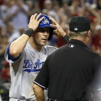 Photo - Los Angeles Dodgers' Michael Young, left, shows his disbelief after being called out on a play at home plate by umpire Joe West in the sixth inning during a baseball game against the Arizona Diamondbacks on Wednesday, Sept. 18, 2013, in Phoenix. (AP Photo/Ross D. Franklin)