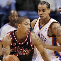 Photo - Chicago's Derrick Rose (1) dribbles past Thabo Sefolosha (2) of Oklahoma City in the second half of the NBA basketball game between the Chicago Bulls and the Oklahoma City Thunder at the Ford Center in Oklahoma City, Wednesday, March 18, 2009. Chicago won, 103-96. PHOTO BY NATE BILLINGS, THE OKLAHOMAN ORG XMIT: KOD