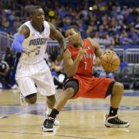 Photo - Toronto Raptors guard Kyle Lowry (7) makes a move to get around Orlando Magic's Victor Oladipo (5) during the first half of an NBA basketball game in Orlando, Fla., Sunday, March 30, 2014. (AP Photo/John Raoux)