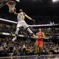 Photo - Indiana Pacers forward Paul George (24) dunks infront of the Los Angeles Clippers Hedo Turkoglu (8) and Jamal Crawford (11) during the second half of an NBA basketball game in Indianapolis, Saturday, Jan. 18, 2014. The Pacers won 106-92. (AP Photo/AJ Mast)