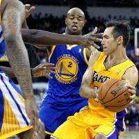 Photo -   Los Angeles Lakers' Steve Nash, right, looks to pass against Golden State Warriors defenders including Jarrett Jack (2) during the first half of a preseason NBA basketball game in Fresno, Calif., Sunday, Oct. 7, 2012. (AP Photo/Gary Kazanjian)