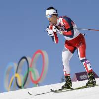 Photo - Norway's gold medal winner Marit Bjoergen skis past the Olympic rings during the women's cross-country 15k skiathlon at the 2014 Winter Olympics, Saturday, Feb. 8, 2014, in Krasnaya Polyana, Russia. (AP Photo/Lee Jin-man)