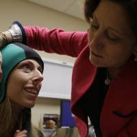Photo - In this Wednesday, July 10, 2013, photo, Dr. Hope Rugo, right, an oncologist and breast cancer specialist, demonstrates the use of the Dignitana DigniCap system on Katherine Serrurier, a research assistant and pre-medical intern, at the University of California San Francisco Mount Zion Hospital cancer center in San Francisco. The caps chill the head and scalp allowing for hair preservation in chemo treatments. (AP Photo/Eric Risberg)