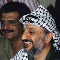 Photo -   FILE - This photo shows Yasser Arafat, PLO leader shown smiling, taken in Beirut, Lebanon, in an August 1981 file photo. A Palestinian official says the remains of former Palestinian leader Yasser Arafat will be exhumed on Tuesday Nov. 27, 2012 to enable foreign experts to take samples as part of a probe into his death. (AP Photo/ Zuheir Saade, File)
