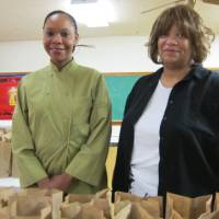 Photo - Demetra Bailey-Stewart, left, owner of B&B Catering, and Sarafia Fleming pose for a picture as free lunches for children are packed at B&B Catering's central kitchen site, 3401 NE 16, for the Oklahoma Southeast Jurisdiction of the Church of God in Christ.  Photo by Carla Hinton, The Oklahoman