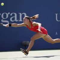 Photo - Aleksandra Krunic, of Serbia, returns a shot against Petra Kvitova, of the Czech Republic, during the third round of the 2014 U.S. Open tennis tournament, Saturday, Aug. 30, 2014, in New York. (AP Photo/Kathy Willens)