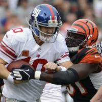 Photo -   New York Giants quarterback Eli Manning (10) is sacked by Cincinnati Bengals defensive end Robert Geathers (91) in the first half of an NFL football game on Sunday, Nov. 11, 2012, in Cincinnati. (AP Photo/Michael Keating)