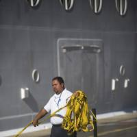 Photo - A West Indian Company employee removes a yellow caution barricade tape from around the Royal Caribbean International's Explorer of the Seas crusie ship, docked at Charlotte Amalie Harbor in St. Thomas, United States Virgin Islands, Sunday, Jan. 26, 2014. U.S. health officials have boarded the cruise ship to investigate an illness outbreak that has stricken at least 300 people with gastrointestinal symptoms including vomiting and diarrhea. (AP Photo/Thomas Layer)