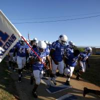 Photo -  Millwood runs down the concrete ramp on to the field before a football game last season.