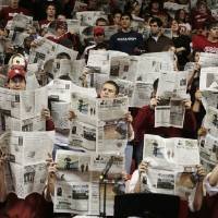 Photo - University of Oklahoma fans in the student section hold up newspapers during team introductions for American University prior to an NCAA men's college basketball game against OU in Norman, Okla., Friday, Nov. 14, 2008. OU is encouraging students to come to the games with a new ticket policy. (AP Photo/Sue Ogrocki) ORG XMIT: OKSO105