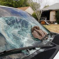 Photo - A car window was broken outside a home damaged by a firebomb Wednesday.  Photo by Paul B. Southerland, The Oklahoman