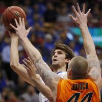 Photo - Kansas center Jeff Withey (5) is fouled by Oklahoma State center Philip Jurick (44) during the first half of an NCAA college basketball game in Lawrence, Kan., Saturday, Feb. 2, 2013. (AP Photo/Orlin Wagner) ORG XMIT: KSOW101