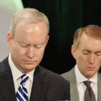 Photo -  Oklahoma City Mayor Mick Cornett and Rep. James Lankford, R-Oklahoma City, bow their heads in prayer Tuesday at the 31st annual Metro Prayer Breakfast in downtown Oklahoma City. Photo by Paul B. Southerland, The Oklahoman   PAUL B. SOUTHERLAND