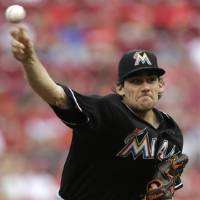 Photo - Miami Marlins starting pitcher Nathan Eovaldi throws against the Cincinnati Reds in the first inning of a baseball game, Friday, Aug. 8, 2014, in Cincinnati. (AP Photo/Al Behrman)